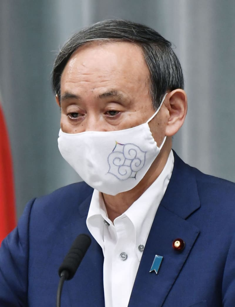 アイヌ文様の刺しゅうが入った布マスクを着用して記者会見する菅官房長官=7日、首相官邸