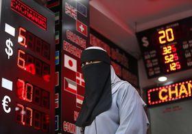 13日、トルコ・イスタンブールの通貨取引所を出る女性(AP=共同)