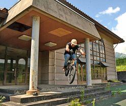 スケートパーク整備の計画を描く旧江尾小学校米原分校で、BMXの技を披露するプロライダーの冨永勇太さん