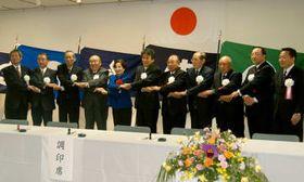 合併協定書に調印後、握手を交わす天草2市8町の市町長ら。左から6人目が安田本渡市長、同5人目は潮谷知事=2005年1月、本渡市民センター