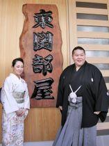 部屋開きを終え、看板の前でポーズをとる東関親方と真充夫人=18日、東京都葛飾区