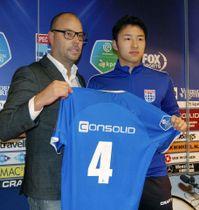 オランダ1部リーグのズウォレに移籍し、記者会見でユニホームを手にする中山(右)=15日、ズウォレ(共同)