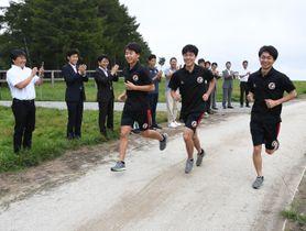 式典出席者の拍手を受け、クロスカントリーコースを走る国学院大の陸上競技部員