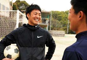 グラウンドで選手(手前)と笑顔で話す平石さん