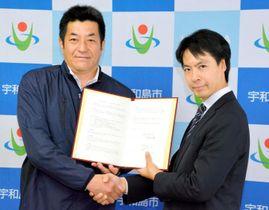宇和島市復興まちづくりアドバイザーの委嘱を受けたRCFの藤沢烈代表(右)=19日午後、同市曙町