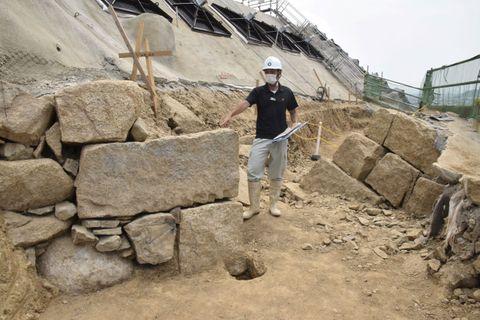 手前と奥に二つ確認された埋没石垣を説明する丸亀市の担当者=丸亀城