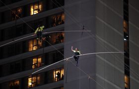 23日、米ニューヨーク中心部で、綱渡りに挑戦するニック・ワレンダさん(右)と姉のリヤーナさん(AP=共同)