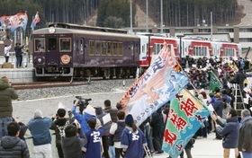 大漁旗を手にした人たちに迎えられ、鵜住居駅に到着した三陸鉄道リアス線の記念列車=23日午前、岩手県釜石市