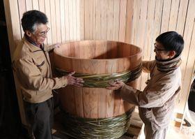 完成した木桶を工場に設置する山中代表(左)と宮崎さん=雲仙市、山中商店