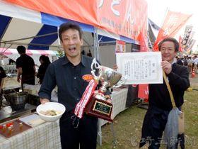 熊谷うどんのブース前で、グランプリのトロフィーを掲げて喜ぶ田野隆広さん(左)=11日午後、埼玉県熊谷市上川上の熊谷スポーツ文化公園