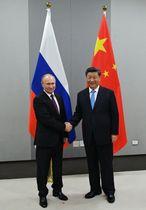 13日、BRICS首脳会議開催地のブラジリアで握手をするロシアのプーチン大統領(左)と中国の習近平国家主席(AP=共同)