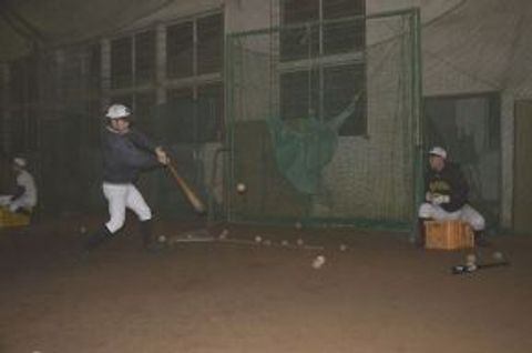 屋内練習場で打ち込みをする知内高の野球部員たち
