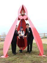 モニュメントの除幕式で、鐘を鳴らすデザイン作者の木村夏海さん(中央)ら=10日、小千谷市山本