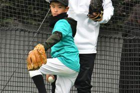 キャッチボールをする小学生に正しい投げ方を指導する山崎=川崎市高津区