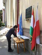 19日、タジキスタン・ドゥシャンベのUNDP事務所前で、秋野豊さんらの慰霊碑に献花する北岡元・駐タジキスタン大使(日本大使館提供・共同)