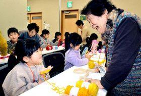 「指編み」で交流を深め、笑顔の児童と高齢者