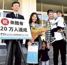 山本晃弘副館長(左)から花束を贈られた来場20万人目の川島さん家族=21日午前、静岡市駿河区