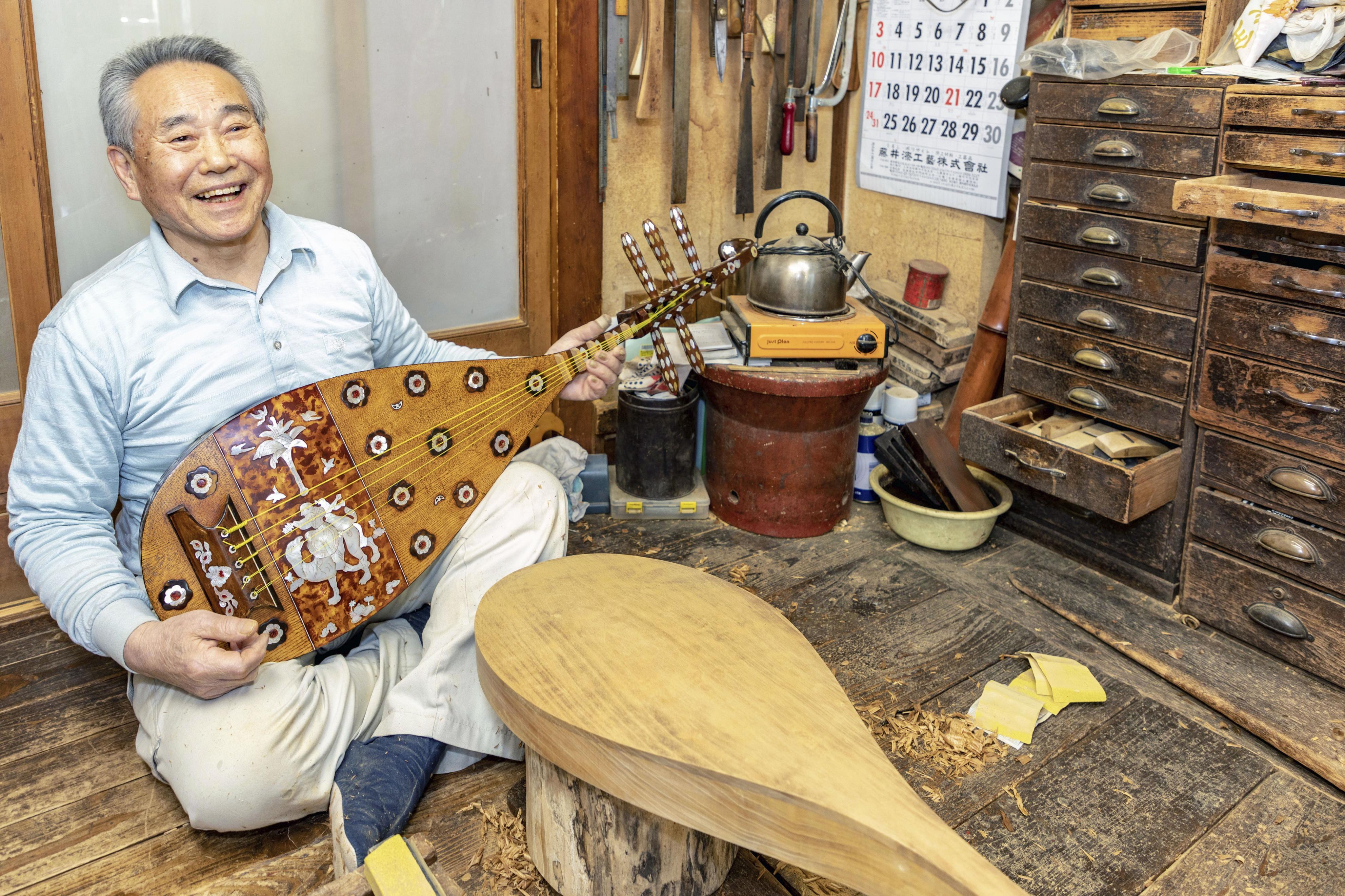年期の入った仕事場で、正倉院宝物を模して製作した琵琶を手に笑顔の四世石田不識。螺鈿などの技法を使い美しく装飾されている=東京・虎ノ門