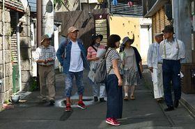 歴史を振り返りながら、なじみ深い街を巡り歩くツアー参加者ら