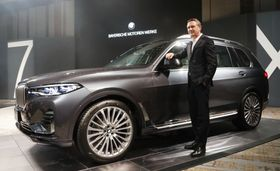 BMWの新型SUV「X7」と日本法人のペーター・クロンシュナーブル社長=24日、東京都港区