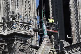 19日、パリのノートルダム寺院で彫像を運び出す準備をする作業員ら(AP=共同)
