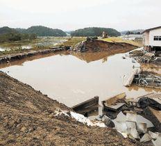 決壊した吉田川(左)の堤防=14日午後3時40分ごろ、宮城県大郷町粕川地区
