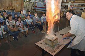 ビニール袋の中で舞い上がった小麦粉が瞬間的に燃え上がる粉じん爆発の実験を見学する参加者ら=三沢航空科学館