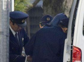 送検のためフードをかぶり車に乗る岡田加津吉容疑者(右手前から2人目)=24日午前9時40分、佐賀北署