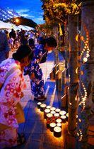幻想的な竹あかりに誘われて、ゆかた姿で訪れた高校生ら=6日、那覇新都心公園の「水の道」