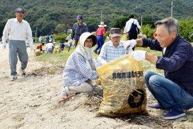 瀬戸内国際芸術祭の会場になる海岸を清掃する住民ら=丸亀市、本島