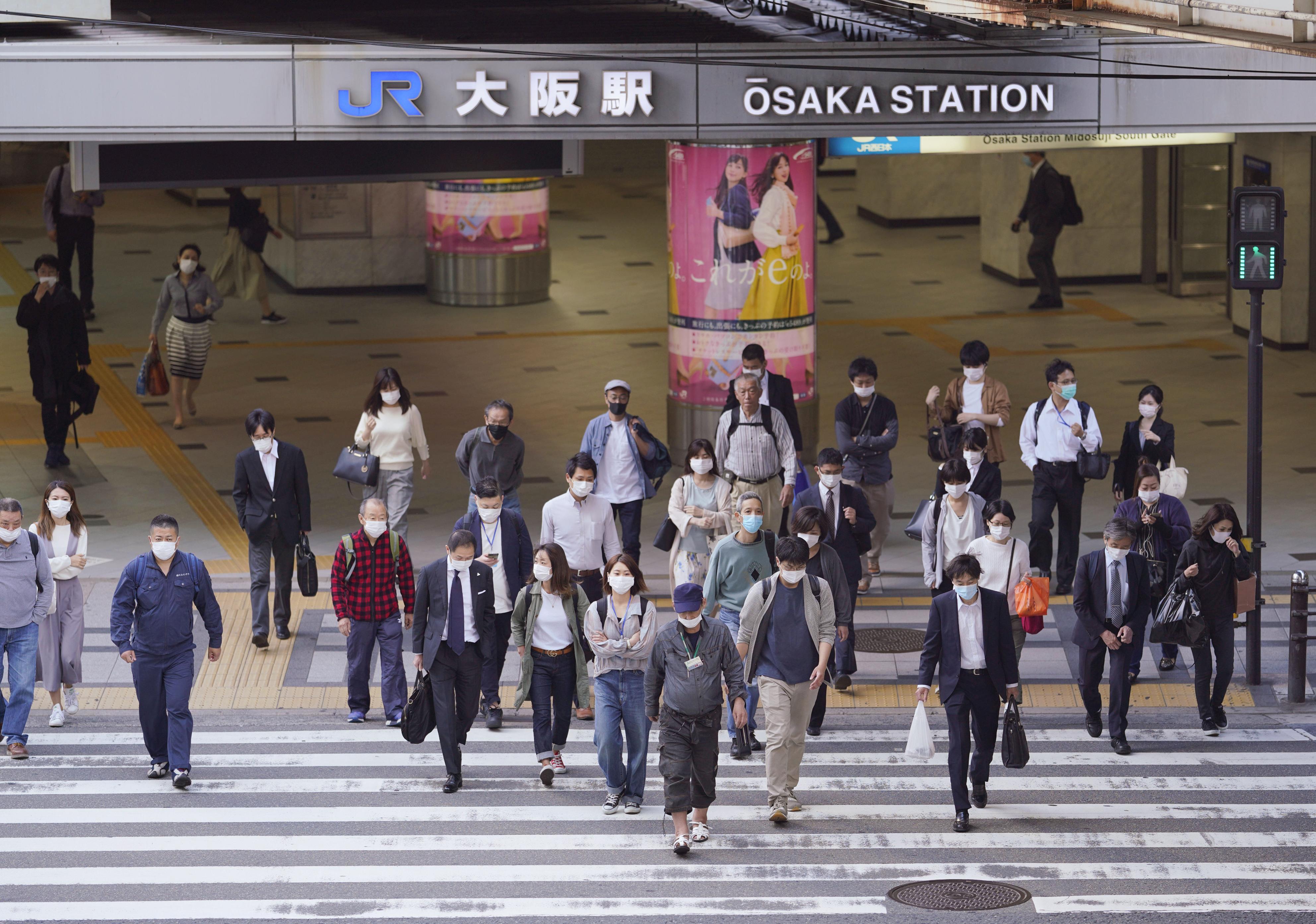 マスク姿で通勤する人たち=21日午前、大阪・梅田