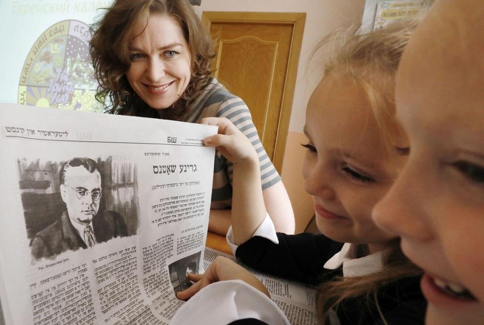 シナゴーグ(ユダヤ教会堂)で行われるイディッシュ語の授業で「ビロビジャネール・シュテルン」紙を紹介するエレナ・サラシェフスカヤ(左)。「子供たちに興味を持ってもらうことはとても重要」と話す。新聞製作の合間にこうした授業や教科書作りなど、次世代への言語継承にも取り組む=ロシア・ビロビジャン(撮影・山下和彦、共同)
