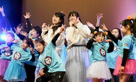 「いくどはぁ☆なみぃ」を歌い終え、笑顔の松田さん(中央左)、及川さん(同右)と、歌に合わせて踊った浪江町と南相馬市の子ども