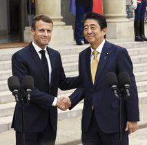 共同記者発表を終え、フランスのマクロン大統領(左)と握手を交わす安倍首相=17日、パリの大統領府(共同)