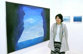 「油彩とアクリルを使い、何度も塗り重ねて仕上げる」と語る永野未来(高知市桜井町1丁目の「ギャラリーE」)
