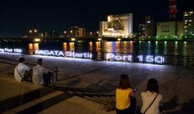 信濃川沿いの夜景に光を添える万代テラスのライトアップ=13日、新潟市中央区