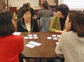 選んだ「もしバナゲーム」のカードを並べ、理由などを話し合う参加者=名古屋市南区で