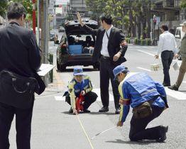 乗用車が暴走し母子2人が死亡した事故で、現場付近を調べる警視庁の捜査員=20日午前、東京都豊島区