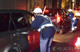 ドライバーの飲酒の有無を確認する警察官=7日午後、さいたま市浦和区仲町