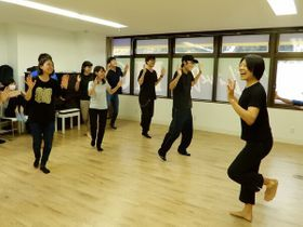 ミュージカル公演に向け、おどるなつこさん(右)と練習する若者たち =横浜市磯子区
