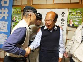 行田市長選で初当選し、支持者と握手を交わす石井直彦氏(右)=21日午後11時すぎ、行田市西新町の選挙事務所