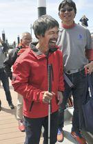 無寄港での太平洋横断に成功し、支援者と談笑する全盲のセーラー岩本光弘さん=20日、福島県いわき市