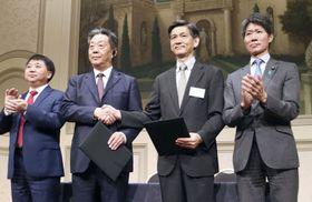 自動運転など次世代車の技術開発で協力の覚書を締結した日本自動車工業会(右側)と中国自動車工業協会の関係者=12日、東京都港区