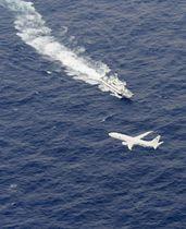 米海兵隊岩国基地所属機が墜落した高知県沖で、捜索活動をする海上保安庁の船と米軍機=6日午後1時30分(共同通信社機から)