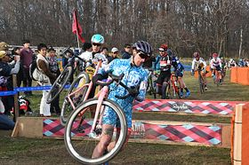「UCI1」の男子レースで自転車を持って障害物を乗り越える選手