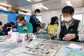 写真洗浄に取り組むボランティア=2月24日、倉敷市災害ボランティアセンター