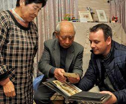 豊島一さんの写真を収めたアルバムを眺めるオコネルさん(右)と昌三さん(中央)ら=三豊市高瀬町