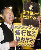 東京・日比谷公園の集会で高度プロフェッショナル制度の創設反対などを訴える参加者=22日夜