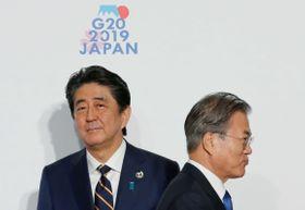 6月、G20大阪サミットで握手した後、すれ違う韓国の文在寅大統領(右)と安倍首相=大阪市(ロイター=共同)
