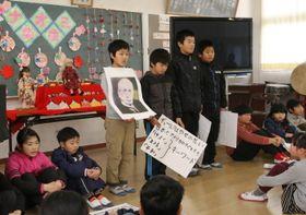 ギューリック博士の写真を示し、日米親善人形の歴史について発表する4年生。奥の人形は(左から)カゥラとナオミ=対馬市、市立西小